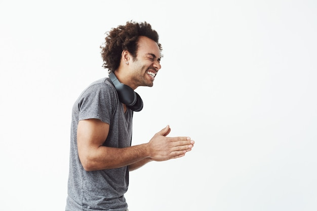 Cheerful african man with headphones laughing standing in profile