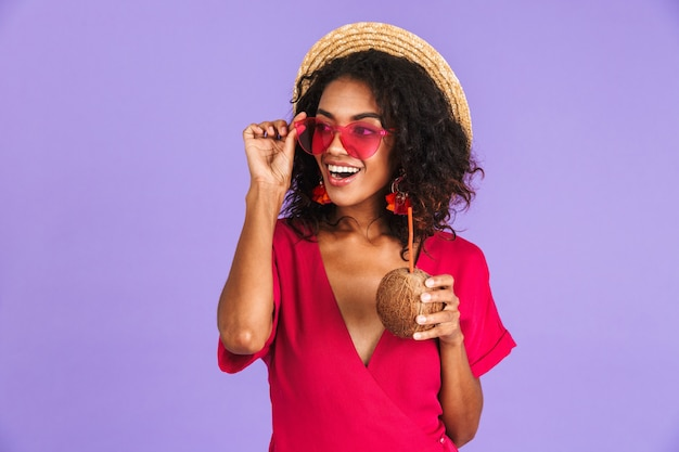 Cheerful african woman in dress, straw hat and sunglasses posing with cocktail while looking away over purple wall