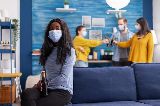 社会的距離を置いた後の安全対策として、covid19の蔓延を防ぐためにフェイスマスクを着用して社会的距離を保ちながら友人と時間を楽しんでいる陽気なアフリカの女性。