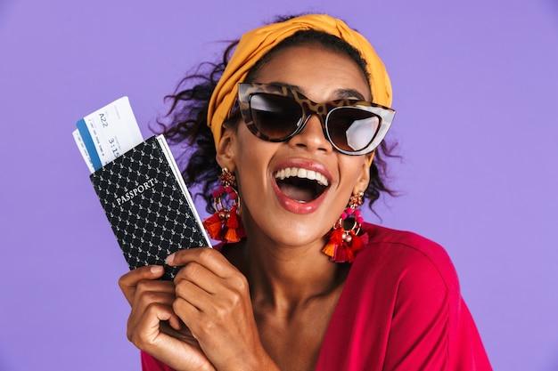 Веселая африканская женщина в платье и солнцезащитных очках держит паспорт с билетами