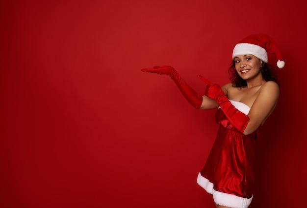 산타 카니발 의상을 입은 쾌활한 아프리카 여성은 손바닥에 가상의 복사 공간을 들고 크리스마스와 새해 광고를 위한 복사 공간이 있는 빨간색 배경 위에 격리되어 있습니다.