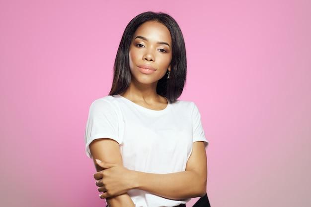 陽気なアフリカの女性の長い髪の白いtシャツホームピンクの背景