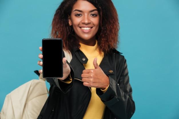 携帯電話の表示を示す陽気なアフリカの女性学生