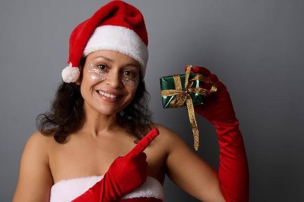 밝은 녹색 포장지와 황금빛 활로 된 크리스마스 선물 상자에 손가락으로 산타 포인트로 옷을 입고 눈 밑에 화장 패치를 한 쾌활한 아프리카 여성이 카메라를 보며 미소를 짓고 있습니다. 복사 공간