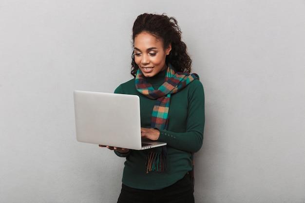 Веселая африканская женщина в шарфе стоит изолированно, держа портативный компьютер