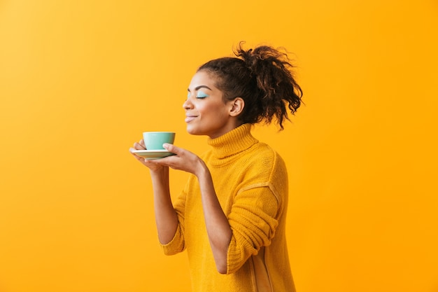 Веселая африканская женщина в свитере держит чашку на изолированном блюдце