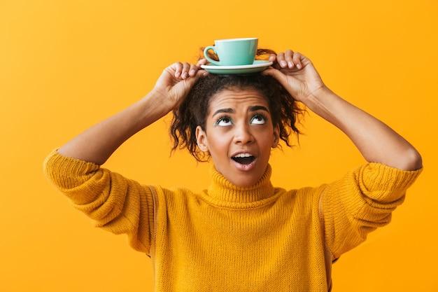 Веселая африканская женщина в свитере держит чашку с блюдцем на изолированной голове