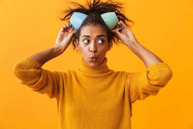 Веселая африканская женщина в свитере держит чашки на голове изолированы