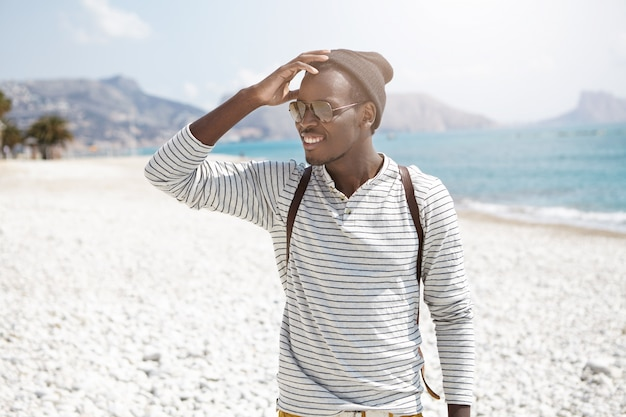 Cheerful african young man standing on beach and looking aside with delightful smile, noticed his friend coming, touching head. summer vacations and adventures. people, lifestyle and traveling