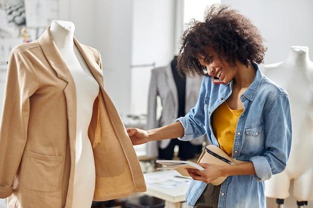 陽気なアフリカ系アメリカ人の女性デザイナーがワークショップで新しいジャケットをチェックするスマートフォンで話します