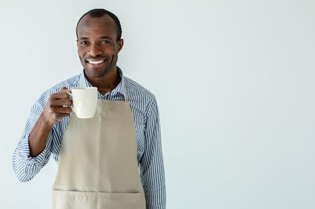 Веселый афро-американский владелец кафе пьет кофе, стоя у белой стены
