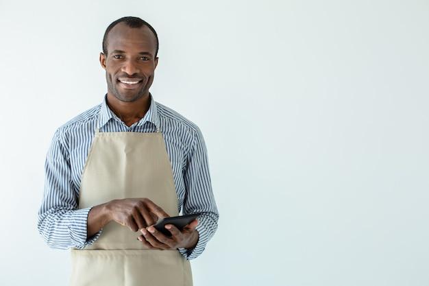 Веселый афро-американский владелец кафе улыбается, стоя у белой стены