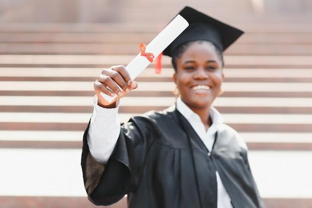 Веселая афро-американская выпускница стоит перед зданием университета