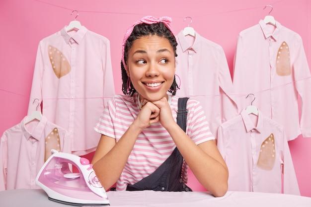 ドレッドヘアを持つ陽気なアフリカ系アメリカ人の女の子がアイロン台に寄りかかって微笑む広い目をそらします洗濯室で家事スタンドをしている忙しい服はヘッドバンドのtシャツとオーバーオールを着ています。