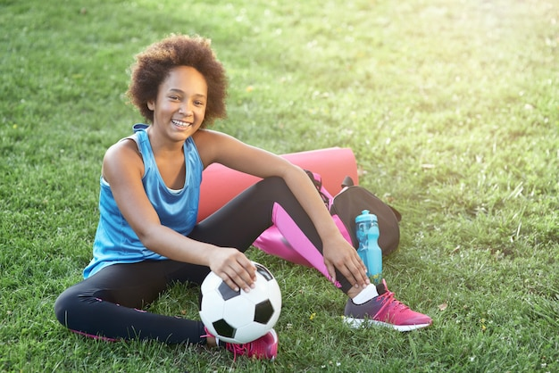 Cheerful afro american girl with soccer ball sitting on grass