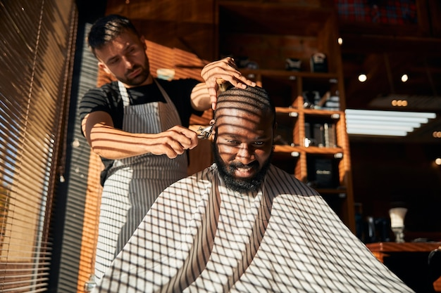 理髪店で散髪をしている陽気なアフロアメリカ人