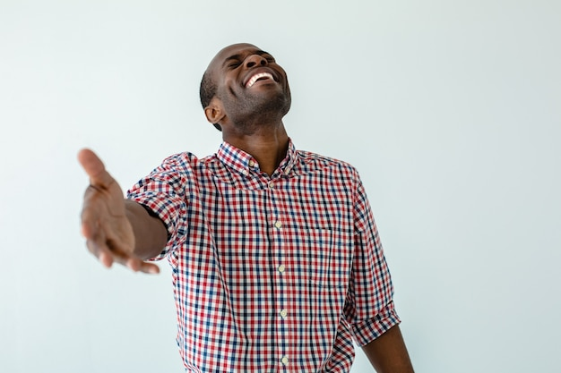 Cheerful afro american man going to make a handshake against white wall