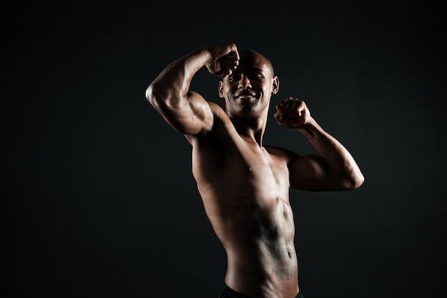 Веселый афроамериканский спортивный человек, показывающий его бицепс