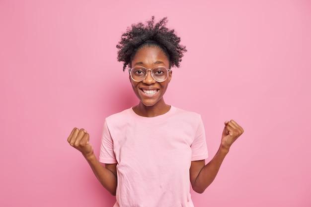 쾌활한 아프리카계 미국인 여성이 우승자를 좋아하는 주먹을 꽉 쥐고 성공을 축하합니다.
