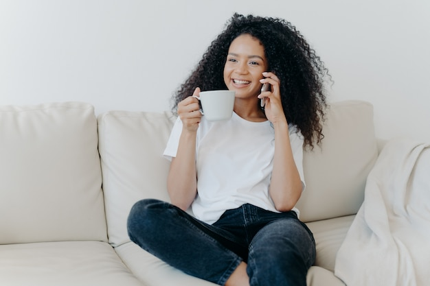 Cheerful afro american woman has coffee break in living room sits on couch calls friend via modern gadget
