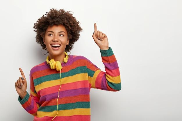陽気なアフリカ系アメリカ人の女性は、人差し指で腕とポイントを上げ、音楽に合わせて楽しく踊り、縞模様の色のセーターとステレオヘッドフォンを身に着け、表情を大喜びし、屋内でモデルを作ります。