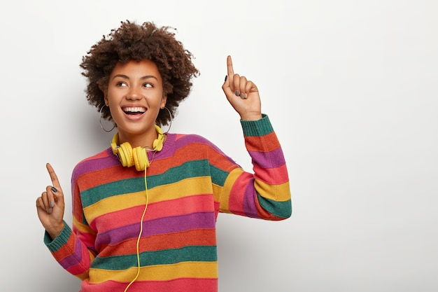 Cheerful afro american woman raises arms and points with index fingers, dances happily to music, wears striped colored sweater and stereo headphones, has overjoyed expression, models indoor.