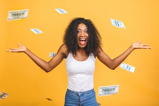 お金で雨の下に立っている陽気なアフロアメリカンの女性
