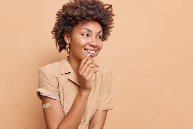 Жизнерадостная афроамериканка с вьющимися волосами счастливо смотрит в сторону, широко улыбается, получает вакцинацию от коронавируса, носит повязку на руке, изолированную над бежевой стеной
