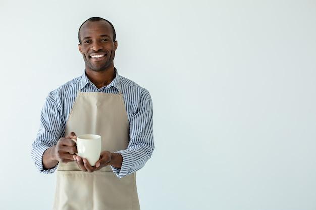 Веселый афроамериканский бариста пьет кофе у белой стены
