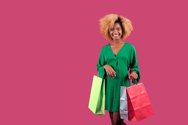Веселая афро женщина, держащая красочные хозяйственные сумки и улыбаясь, стоя на изолированном фоне. концепция продажи черная пятница.