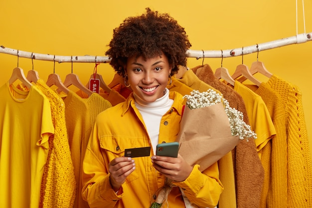 Cheerful afro woman holds mobile, credit card and bouquet, stands against clothes rail