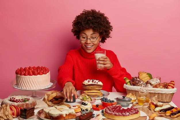 Cheerful afro woman stretches hand to delicious dessert, holds glass of milk, eats cake, surrounded with junk food, wears spectacles and red sweater, cannot say no to sweets