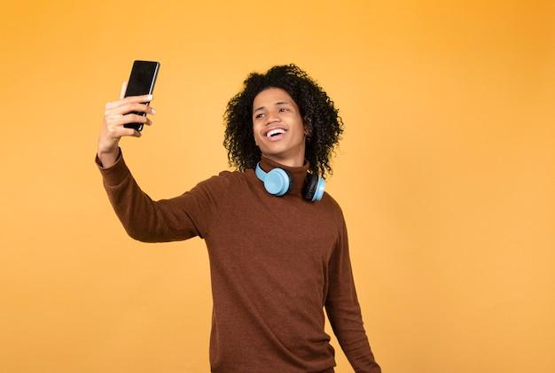 電話で自分撮りをしている陽気なアフロ青年。黄色の背景にカジュアルな服を着たアフリカのティーンエイジャーの写真。