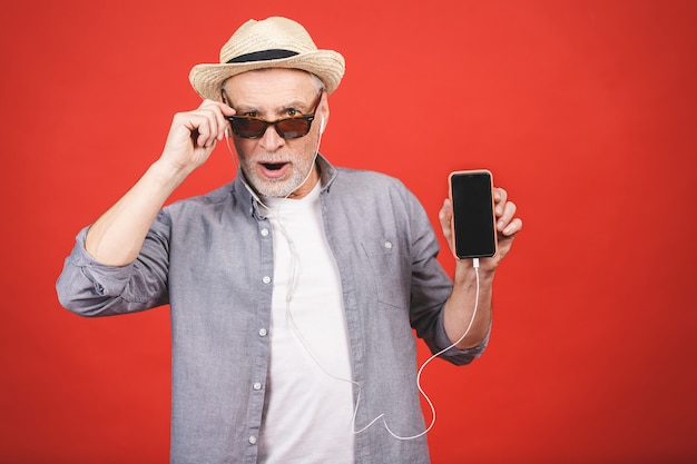 Cheerful aged senior listening to music on a phone isolated.