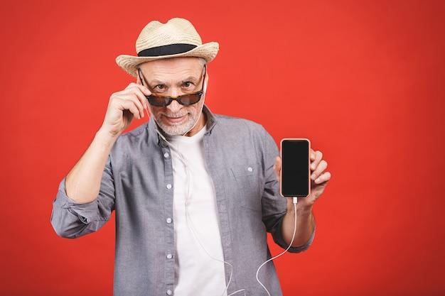Жизнерадостное постаретое старшее слушая к музыке на изолированном телефоне.