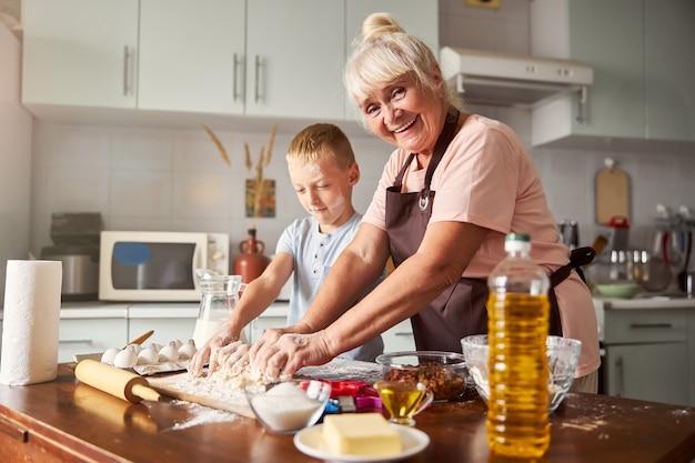 쾌활한 노부인과 부엌에서 요리하는 집중된 소년