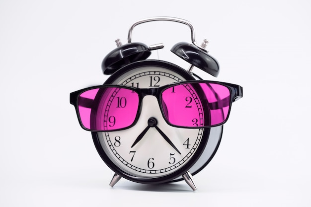 Cheerful alarm clock in pink glasses on a light background.
