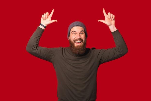 陽気な驚いたあごひげを生やした男が頭上に上を向いています。