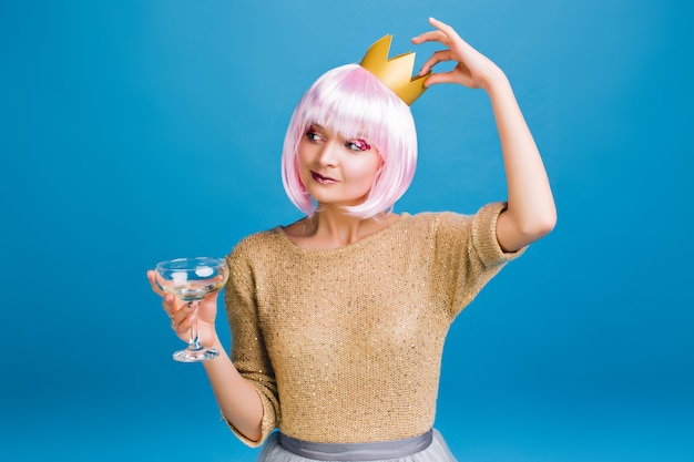 Cheerful amazing young woman with pink haircut having fun . golden crown on head, brightful makeup with pink tinsels, champagne, celebrating new year party, smiling.
