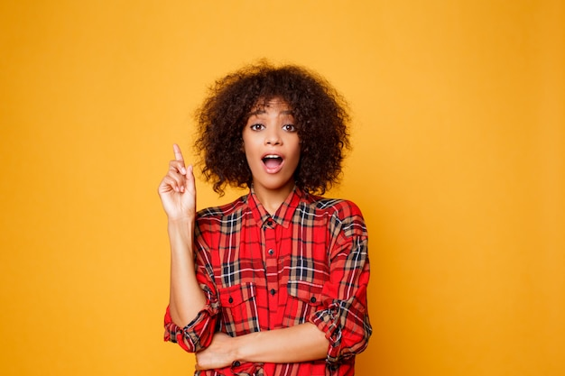 Cheerful american black woman in red  shirt looking on camera  and pointing finger up on copy space isolated over orange background.