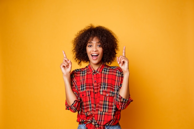 Cheerful american black woman in red  shirt looking upward and pointing fingers up on copy space isolated over orange background.