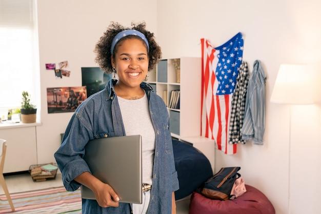 Веселая американская девушка-подросток с ноутбуком, стоя в ее спальне