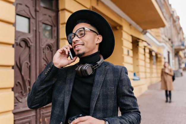 오래 된 건물 근처에 서있는 동안 전화 통화하는 유행 회색 복장에 쾌활 한 미국 사람. 누군가 전화하고 웃고 열정적 인 아프리카 남자.