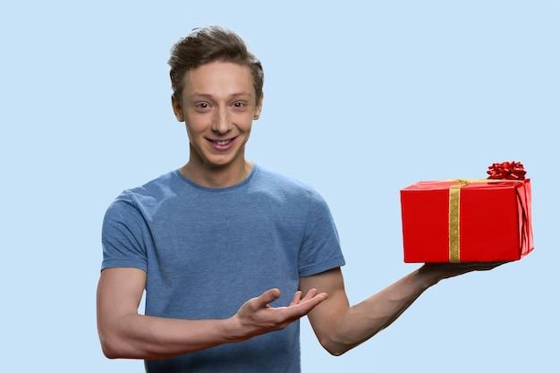 쾌활한 미국 남학생이 빨간색 선물 상자를 제시하고 있습니다.