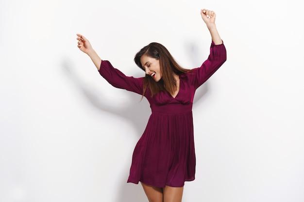 보라색 드레스를 입은 쾌활하고 잘 생긴 매력적인 여성은 파티 나이트 클럽을 즐기고, 편안하게 손을 들고, 머리를 움직이는 리듬 음악을 흔들고, 흰 벽에 서 있습니다.
