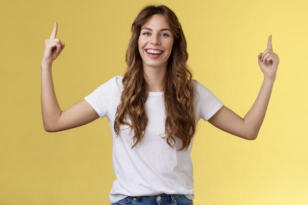 쾌활하고 즐거운 행복한 활기찬 어린 소녀 긴 곱슬 머리는 웃는 이빨 행복한 카메라를 가리키는 손을 들어 올리며 우수한 변형을 소개하여 사이트 링크 광고 노란색 배경을 클릭하도록 제안합니다.