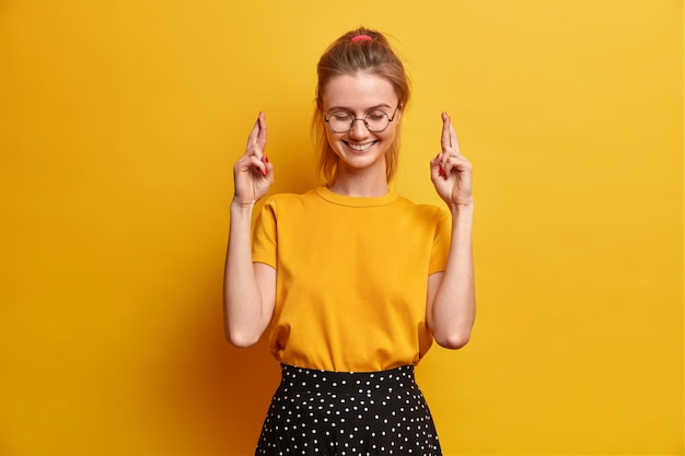쾌활한 즐거운 밀레 니얼 소녀가 손가락을 교차하여 꿈이 이루어지기를 희망하거나 성취 된 미소가 즐거운 소식을 받으면 좋은 소식을받으며 노란색 벽에 고립 된 둥근 투명 안경 티셔츠와 치마를 입습니다.