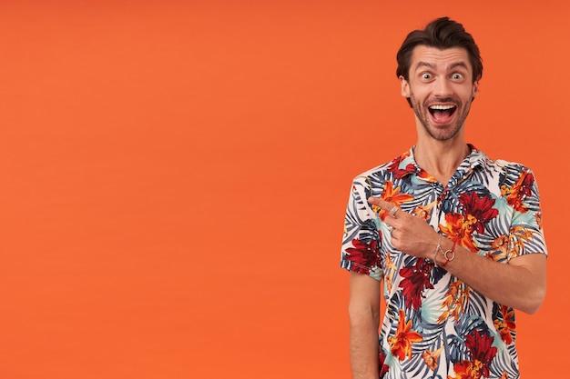하와이안 셔츠에 수염을 가진 쾌활한 재미있는 젊은 남자가 행복해 보이고 손가락으로 빈 공간에서 측면을 가리키는