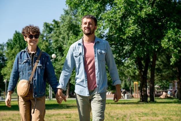 Веселая и ласковая молодая пара в брюках и джинсовых куртках гуляет в общественном парке в солнечный день