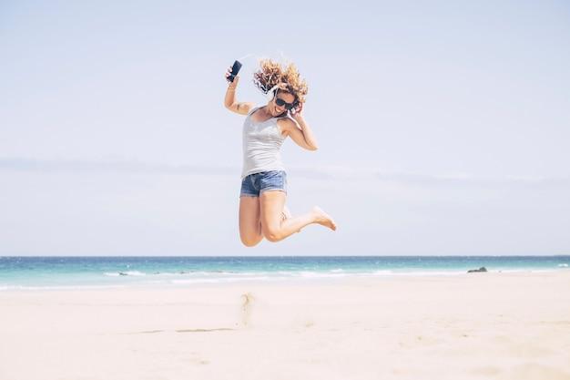 明るく魅力的な白人の若い女性は、ビーチと夏休みを楽しんでいます。砂の上をジャンプする電話とイヤホンで音楽を聴きます。無料の女性のための休日と幸福の概念
